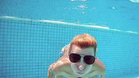 Woman is diving underwater wearing sunglasses. Woman is diving underwater in swimming pool wearing sunglasses. Fun and cute recreation slow motion shot stock video
