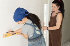 Woman DIY drawing a straight line on a wall royalty free stock photography