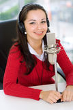 A woman DJ is in front of a mic. In the broadcasting studio Stock Photos
