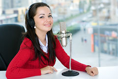 A woman DJ is in front of a mic. In the broadcasting studio Stock Image