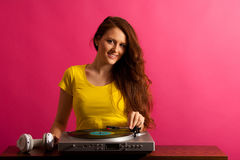 Woman DJ playing on gramophone over pink background Royalty Free Stock Photography