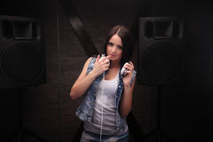 Woman dj with white headphones touching her lip with finger. Loudspeakers on background. Stock Photo