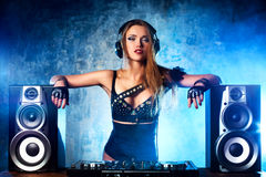 Woman dj. Young woman dj playing music. Big loud speakers, headphones and dj mixer on table royalty free stock images