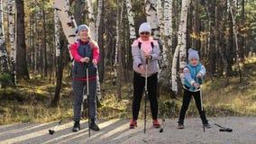 Woman do die Nordic in aard lopen Meisjes en kinderen de stokken van de gebruikstrekking en noordse polen, rugzakken familiereize stock video