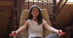 Woman do meditation practice seated on swing hammock lounge chair
