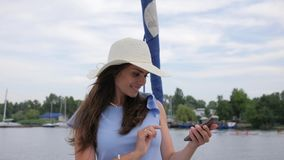 Woman do pictures on mobile phone in open air, female create selfi photo in background sea, video from travel. Nice girl make selfie on yacht, android in hand stock video