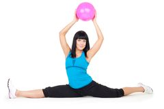 Woman do splits sitting holding ball Royalty Free Stock Photos