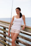 Woman on the dock with a fishing pole Stock Images