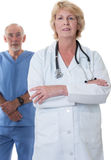 Woman doctor with arms folded, male nurse in back Royalty Free Stock Photos