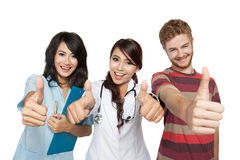 Woman doctor with assistant and man patient thumb up. Closeup portrait women doctor with assistant and men patient, happy, smiling and give you thumb up Stock Photography