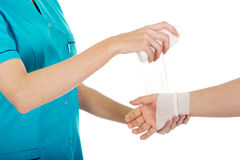 Woman doctor bandaging female hand. Royalty Free Stock Photos