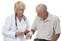 Woman doctor bandaging senior man's wrist Stock Images