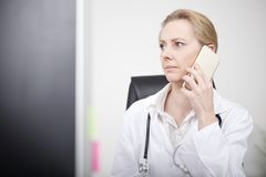 Woman Doctor Calling on Mobile and Looking to Left Royalty Free Stock Photography