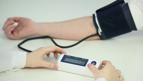 Woman doctor checking patient's blood pressure using sensor, health monitoring. Stock footage stock footage