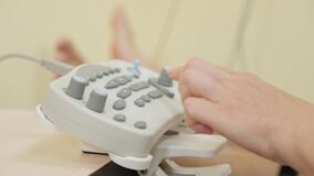 Woman doctor clicks on a device to measure nerve impulses.