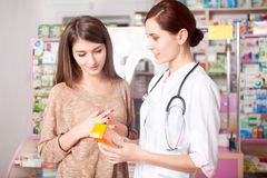 Woman doctor and client inside pharmacy Royalty Free Stock Photography