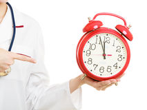 Woman doctor with clock isolated on white Stock Images