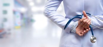Woman doctor crossed arm and holding stethoscope behind back royalty free stock image