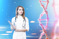 Woman doctor and a dna. Portrait of a red haired woman doctor standing against blue background with a dna chain to her right. Toned image royalty free stock photos