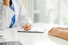 Woman Doctor and Female Patient in Hospital Office. Woman doctor talks to female patient while writing on the patient health record in hospital office stock image