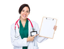 Woman doctor finger point to blank page of clipboard Royalty Free Stock Photography