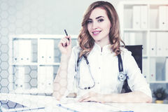 Woman doctor in her office, network. Portrait of a beautiful woman doctor with a stethoscope and red hair sitting at a desk in her office. Toned image, film Stock Photo