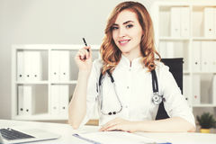 Woman doctor in her office. Portrait of a beautiful woman doctor with a stethoscope and red hair sitting at a desk in her office. Toned image Stock Image
