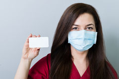 Woman doctor holding a blank white card Stock Image
