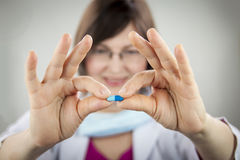 Woman doctor holding blue capsule Royalty Free Stock Photography