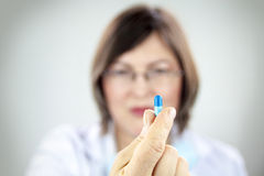 Woman doctor holding blue pill Royalty Free Stock Photography