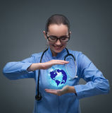 The woman doctor holding earth in globalisation concept. Woman doctor holding earth in globalisation concept royalty free stock photos