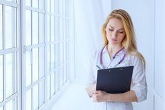 Woman doctor holding pen writing on clipboard for taking patient Stock Image