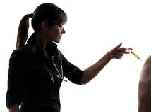 Woman doctor holding surgical needle vaccination silhouette Stock Photo