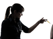 Woman doctor holding surgical needle vaccination silhouette Stock Photography
