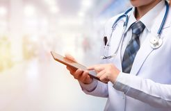 Woman doctor holding tablet and pointing index finger to screen royalty free stock photography