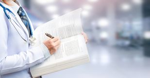 Woman doctor holding textbook and pointing to important content. On blurred patient department of hospital stock photos
