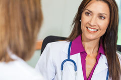 Woman Doctor in Hospital Meeting with Female Colleague. Happy, smiling, women doctor in white lab coat with stethoscope in hospital office meeting with female Royalty Free Stock Images