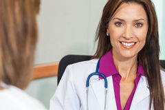Woman Doctor in Hospital Meeting with Female Colleague. Happy, smiling, women doctor in white lab coat with stethoscope in hospital office meeting with female Stock Images