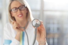 Woman doctor listening with stethoscope stock image