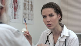 Woman doctor listening to senior patient talking. stock footage