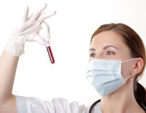Woman doctor looking at a blood sample Royalty Free Stock Image