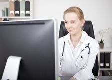 Woman Doctor Looking at Computer Monitor Seriously Royalty Free Stock Photo