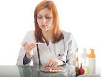 Woman doctor looks at the thermometer Royalty Free Stock Image
