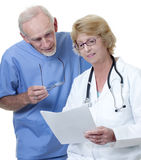 Woman doctor with male medic in scrubs. Woman doctor showing notes to male doctor in scrubs. Isolated on white Royalty Free Stock Image