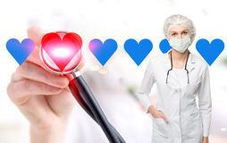 Woman doctor in a mask and blue hearts. Portrait of a woman doctor wearing a uniform and a mask. There is a stethoscope on her shoulders. Close up of a hand and royalty free stock photos