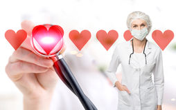 Woman doctor in a mask and red hearts. Portrait of a woman doctor wearing a uniform and a mask. There is a stethoscope on her shoulders. Close up of a hand and a royalty free stock photos