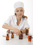 Woman doctor with medication in glass bottles Stock Images