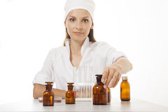 Woman doctor with medication in glass bottles Stock Photos