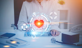 Woman doctor, office, heart HUD. Close up of an unrecognizable woman doctor sitting at her desk with a tablet computer in front of her. A red heart and HUD in stock images