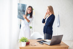 Woman doctor and patient in hospital looking at x-ray film healthcare, roentgen, people medicine concept. Woman doctor and patient in hospital looking at x-ray Royalty Free Stock Image